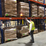 WDS Savannah uses state of the art warehouse management software. Here, an employee is scanning a wrapped pallet of goods on racking.