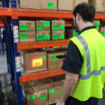 WDS Savannah uses state of the art warehouse management software. Here, an employee is scanning retail consumer goods on racking.